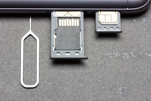 Smartphone mit offenen sim-slots und micro-sd-speicher auf grauem hintergrund