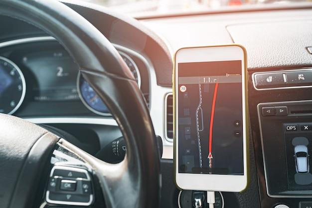 Smartphone mit offener gps-navigations-app auf torpedo im auto