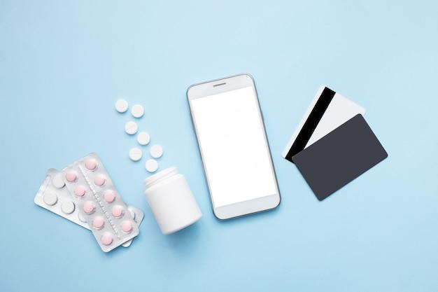 Smartphone mit pillen und kreditkarte auf einem blauen hintergrund. bleib zu hause konzept. online-shopping in der apotheke. flache lage, draufsicht.