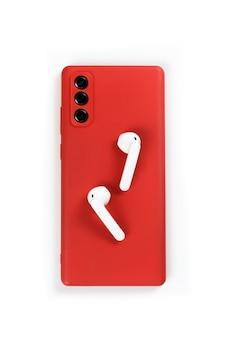 Smartphone mit roter abdeckung und draufsicht des weißen drahtlosen kopfhörers auf weißem hintergrund