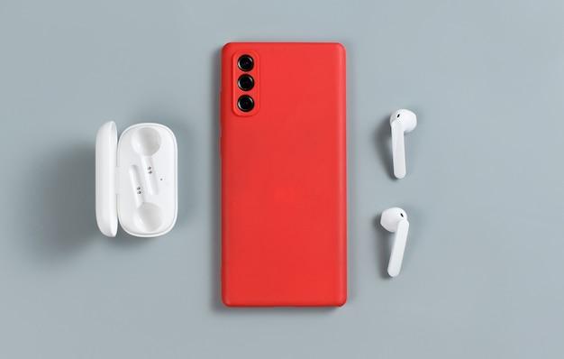 Smartphone mit roter abdeckung und weißen drahtlosen kopfhörern draufsicht auf grauem hintergrund