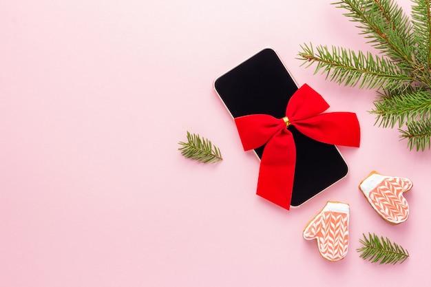 Smartphone mit roter schleife für ein weihnachtsgeschenk auf rosa hintergrund nahe fichte und kekse