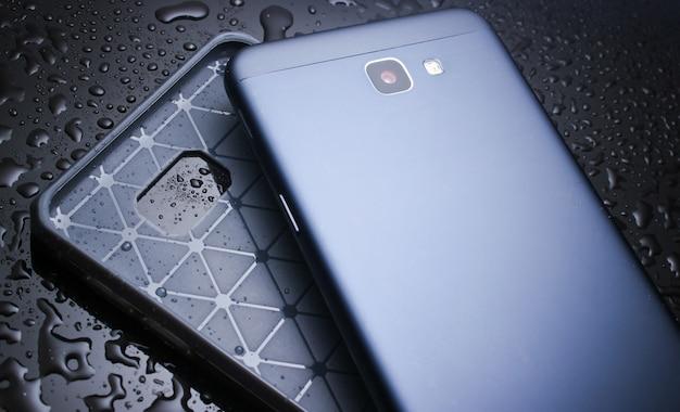 Smartphone mit schutzhülle auf schwarz mit wassertropfen. schützen sie ihr smartphone vor wasser