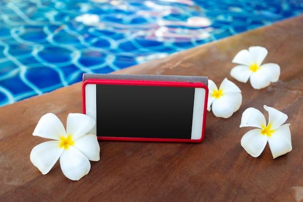Smartphone mit schwarzem bildschirm in der nähe von pool. ferien-konzept