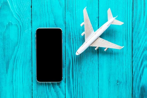 Smartphone, mit schwarzem schirm, flugzeugmodell auf blauem hölzernem