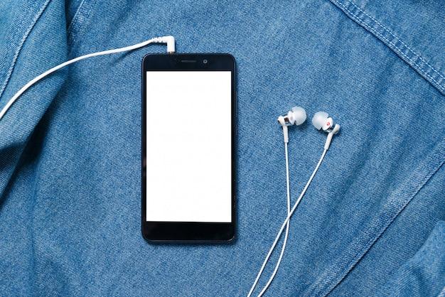 Smartphone mit schwarzer hülle und einem leeren weißen bildschirm und eingesteckten kopfhörer-ohrstöpsel auf denim-hintergrund