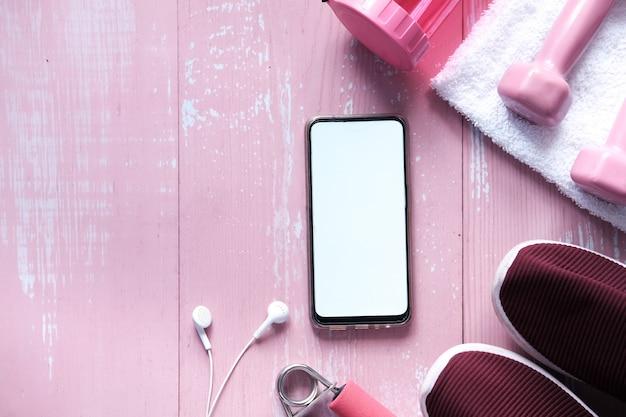 Smartphone mit sportgeräten auf holzboden.