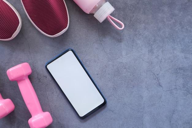 Smartphone mit sportgeräten auf schwarzem hintergrund