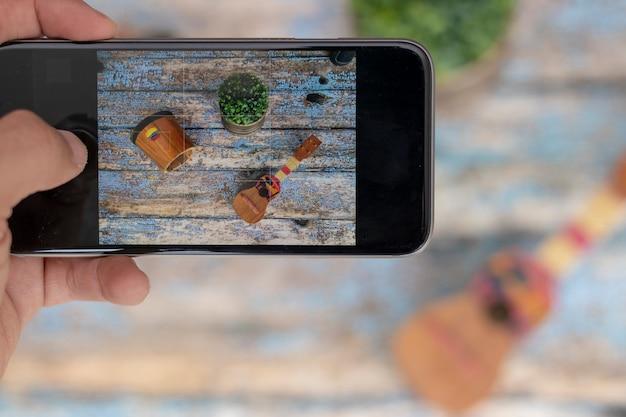 Smartphone mit venezolanischen musikinstrumenten, cuatro und trommel