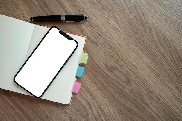 Smartphone mit weißem bildschirm auf notebook