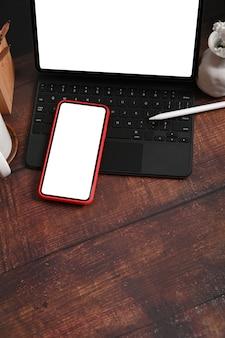 Smartphone mit weißem bildschirm, computer und tablet auf holztisch.