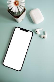 Smartphone mit weißem bildschirm, kopfhörer und blume