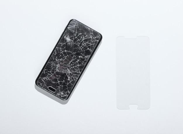 Smartphone mit zerbrochenem neuen schutzglas auf weißem tisch.
