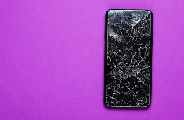 Smartphone mit zerbrochenem schutzglas auf lila tisch. draufsicht