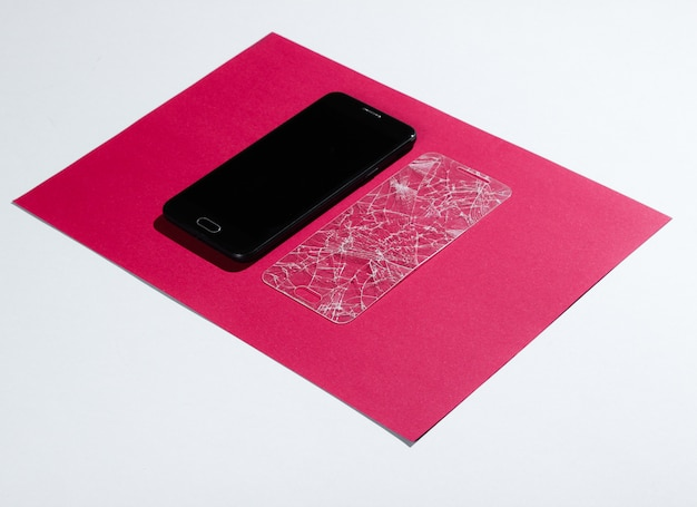 Smartphone mit zerbrochenem schutzglas auf papiertisch. seitenansicht