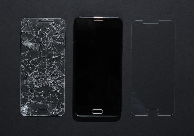 Smartphone mit zerbrochenem und neuem schutzglas auf schwarzem tisch. draufsicht