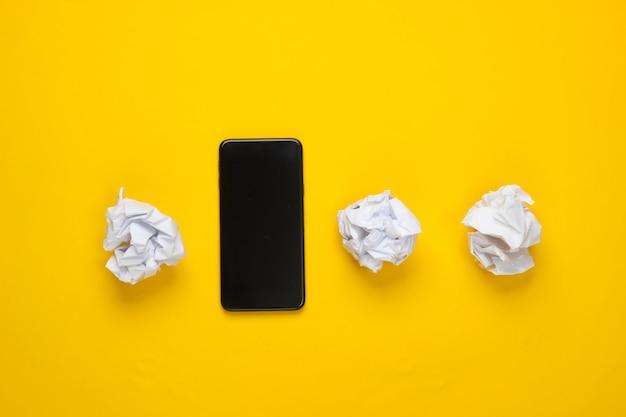 Smartphone mit zerknitterten papierkugeln auf gelber fläche. draufsicht