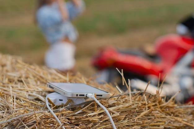 Smartphone-nahaufnahme mit einem tragbaren ladegerät. power bank lädt das telefon vor dem hintergrund eines motorrads, eines mädchens und der natur auf.