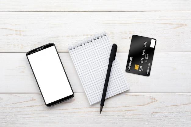 Smartphone, notebook, stift und kreditkarte auf einem weißen tisch