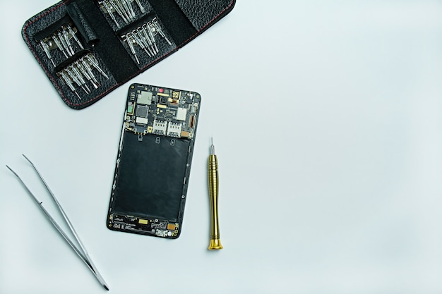 Smartphone reparieren. demontiertes smartphone, schraubendreher zum demontieren des telefons. flachgelegt, draufsicht. platz für text.