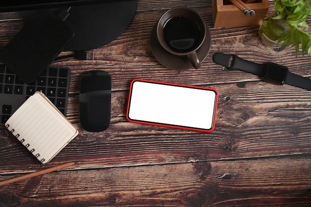 Smartphone, smartwatch, zimmerpflanze und kaffeetasse auf holzschreibtisch.