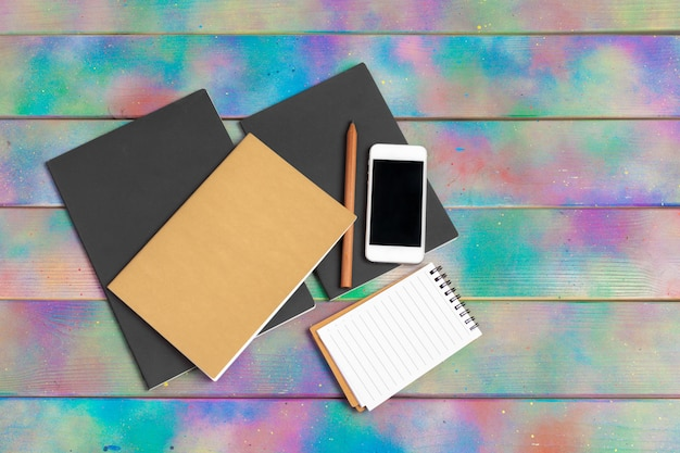 Smartphone, tablette, notizbuchstift auf dem hintergrund eines holztischs