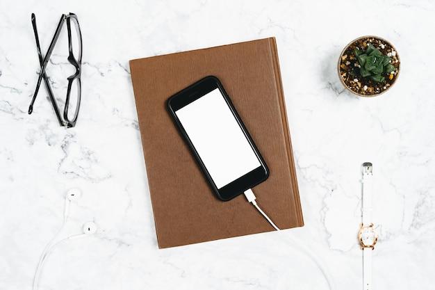 Smartphone trennte weißen schirm mit den verbundenen kopfhörern und dem anmerkungsbuch