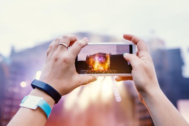 Smartphone über der menge bei einem musikkonzert. lichtshow aufnehmen