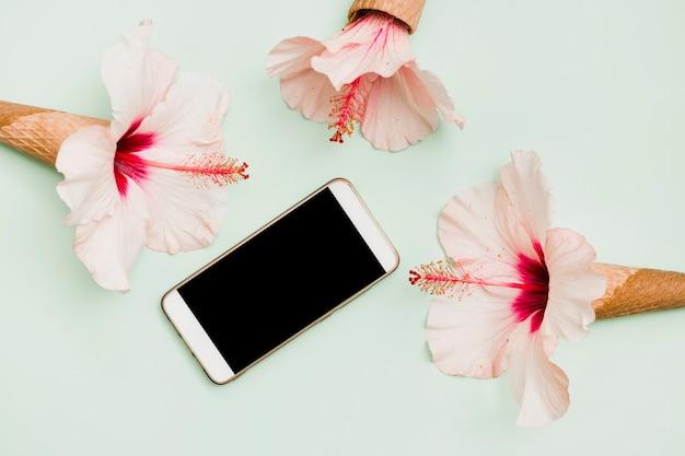 Smartphone umgeben mit hibiskusblüten in waffelhörnern vor farbigem hintergrund