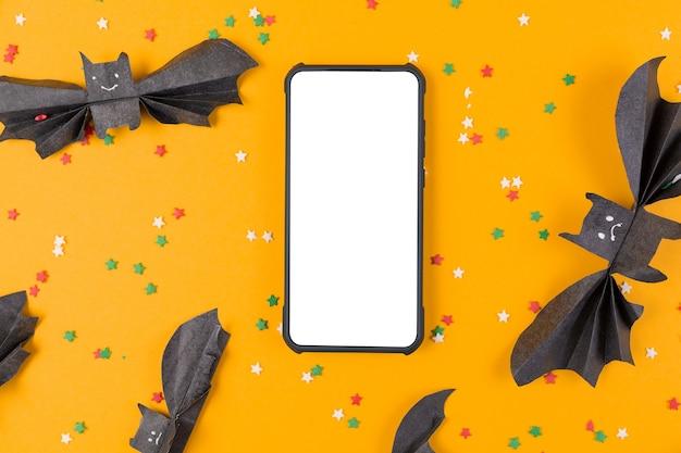 Smartphone umgeben von fledermäusen aus papier auf orange. flach liegen