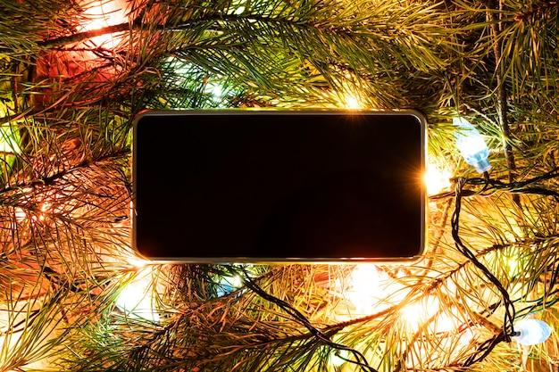 Smartphone umgeben von tannenzweigen. leerer bildschirm für design oder text. weihnachtsdekorationen und technologiekonzept.