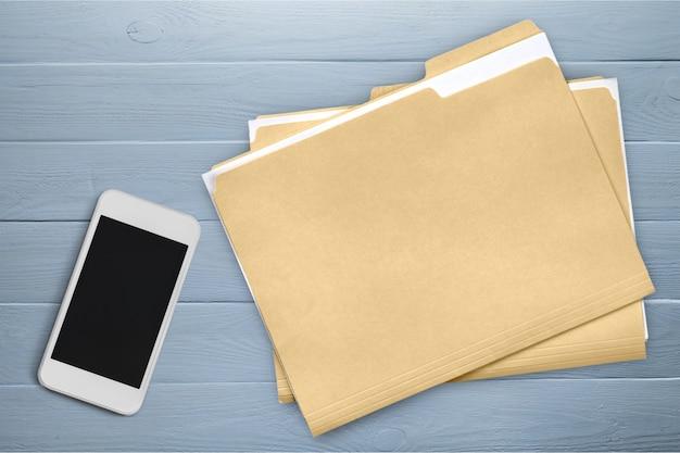 Smartphone- und dokumentenmappen auf holzuntergrund