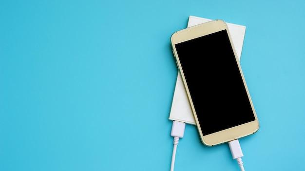 Smartphone und energienbank für das laden von mobilen geräten auf einem blauen hintergrund.