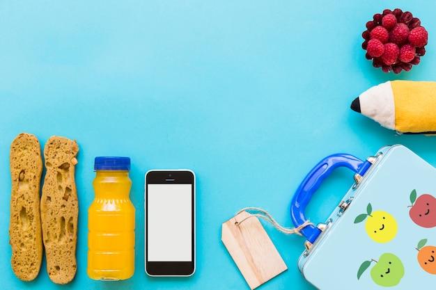 Smartphone und gesundes lebensmittel nahe lunchbox und federmäppchen