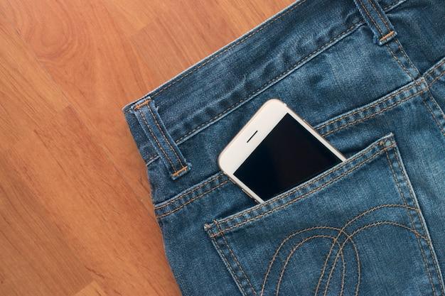 Smartphone und jeans auf bretterboden
