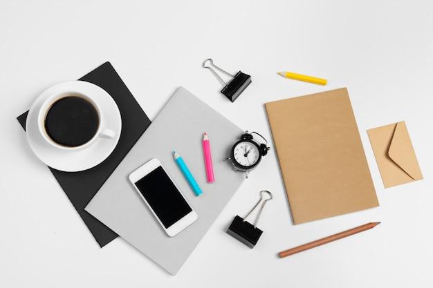 Smartphone und kaffeetasse mit büromaterial