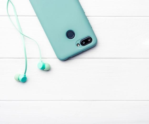 Smartphone und kopfhörer auf dem tisch