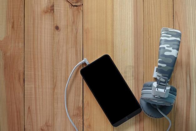 Smartphone und kopfhörer auf hölzernem.