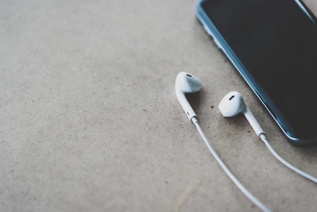 Smartphone und kopfhörer auf holzhintergrund