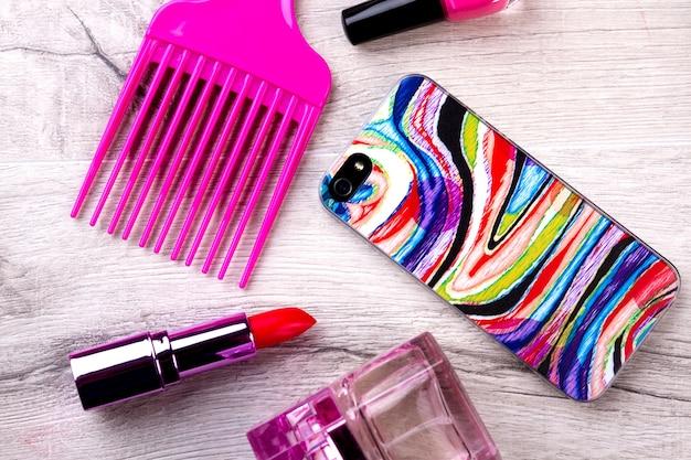 Smartphone und make-up. parfüm, lippenstift und kamm. telefon als modernes accessoire. machen sie sich bereit für eine party.