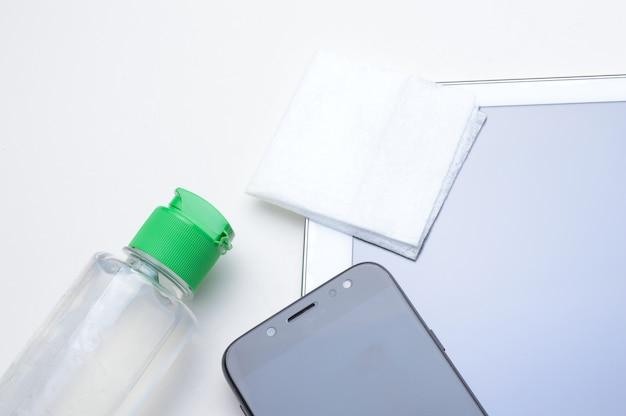 Smartphone und tablet an ort und stelle mit einer flasche gel-desinfektionsmittel und serviette. antivirale und antibakterielle behandlung von tragbaren geräten.