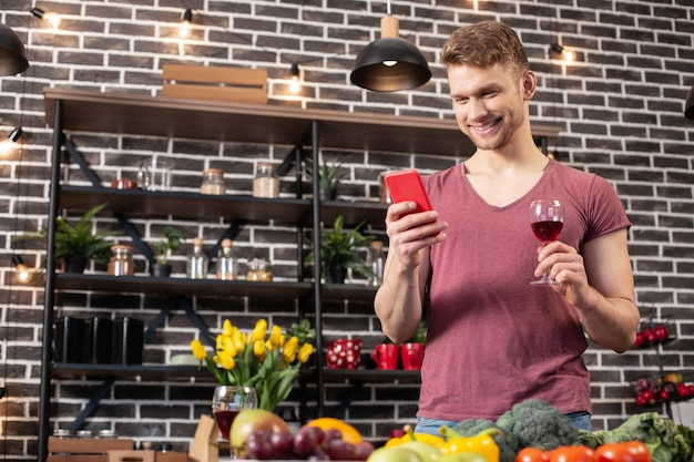 Smartphone und wein. mann, der rotes smartphone und ein glas wein hält, während er zu hause in der küche auf seine freundin wartet
