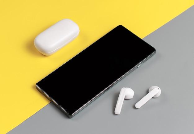 Smartphone und weiße kabellose ohrhörer mit der falloberansicht auf grauem und gelbem hintergrund