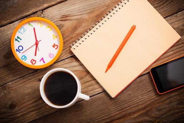 Smartphone, wecker, tasse kaffee und notizbuch auf hölzernem hintergrund