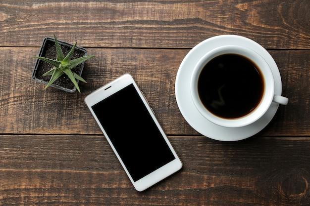 Smartphone weiß und eine tasse kaffee auf einem braunen holztisch. sicht von oben