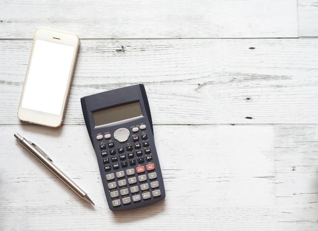 Smartphone weißer bildschirm und silberner stift und taschenrechner auf weißem holztisch draufsicht geschäftskonzept