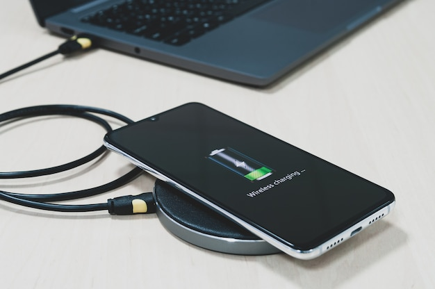 Smartphones werden über ein drahtloses ladegerät aufgeladen