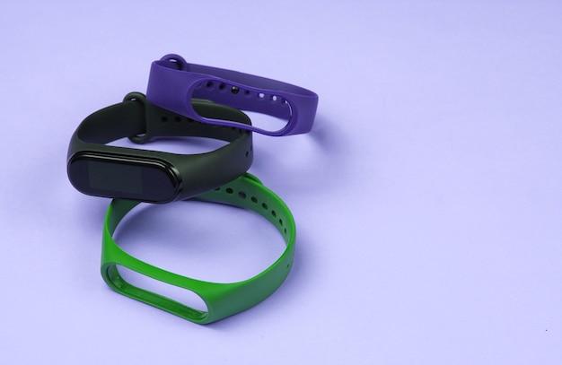 Smartwatch mit austauschbaren armbändern auf violettem hintergrund. fitness-tracker. moderne geräte