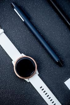 Smartwatch und smart pen auf schwarzem hintergrund