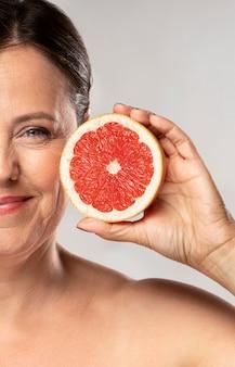 Smiley ältere frau, die die hälfte der grapefruit hält